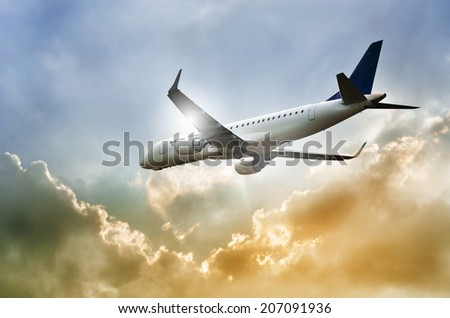 Airplane in the dramatic cloudscape and sunbeams  - stock photo