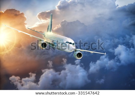Airplane in the sky at amazing colorful sunset