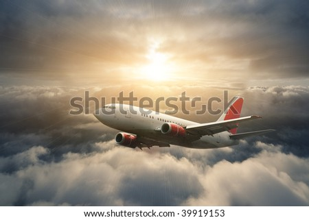 Airplane in the sky at sunset - stock photo