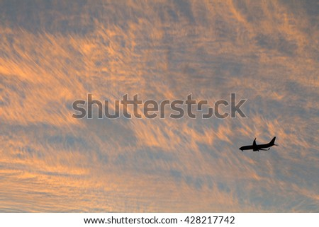 Airplane in the sky at sunset.