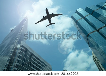 Airplane in the sky with modern buildings - stock photo