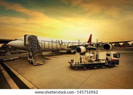 Airplane is being serviced by the ground crew. - stock photo