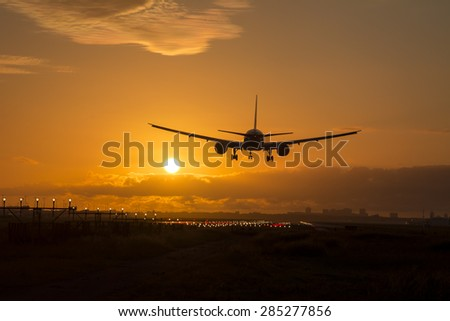 Airplane is landing during a beautiful cloudy sunrise.