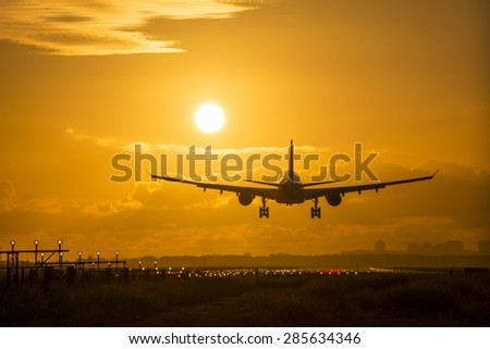 Airplane is landing during a Beautiful cloudy sunrise  - stock photo