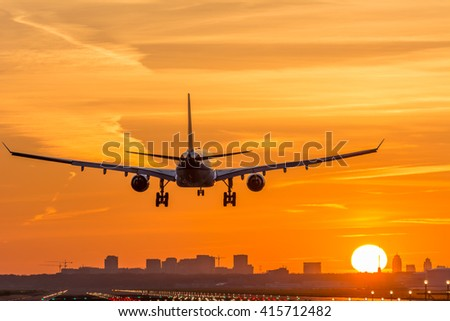 Airplane is landing during a nice early morning sunrise. - stock photo