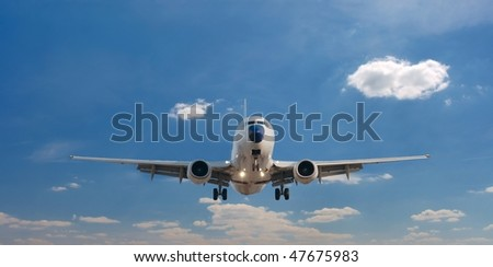 Airplane landing against clear blue sky - stock photo
