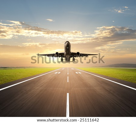airplane landing at airport during dusk hour - stock photo