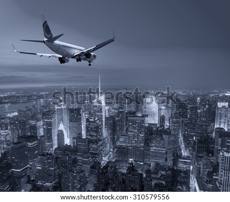 Airplane landing at night in New York City. - stock photo