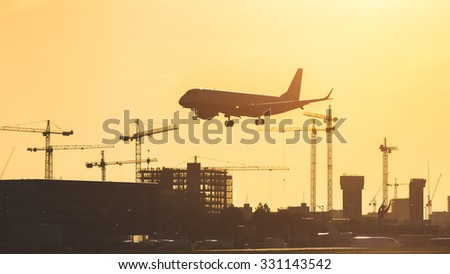 Airplane landing at sunset at London City airport. Silhouette shot with buildings and cranes on background. The plane has gear down already - stock photo