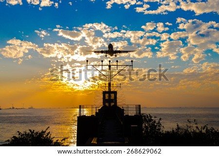 Airplane landing at sunset - Silhouette - stock photo