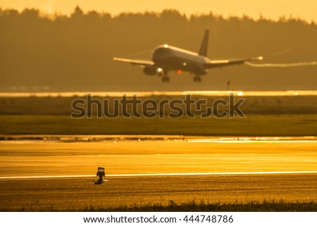 Airplane landing at the airport. Airplane out of focus. Airport runway light in focus - stock photo