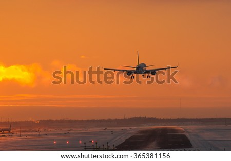 Airplane landing at the airport runway at arctic sunset in winter afternoon in Finland