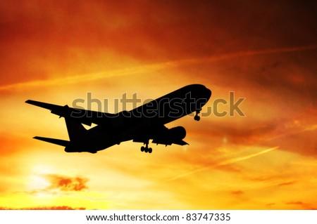 Airplane landing before sunset - stock photo