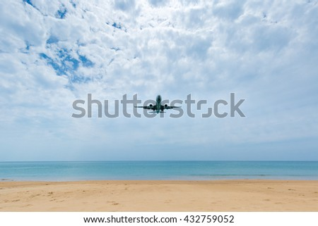 Airplane landing over the sea on cloudy day.