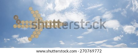 airplane made out of one pound coins with a blue sky background - stock photo