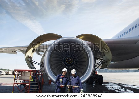 airplane mechanics and giant jet engine repair - stock photo