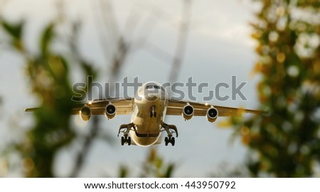 airplane mid air flying over tress landing at airport. modern transportation technology background - stock photo
