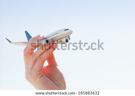 Airplane model in hand on sunny sky. Concepts of travel, transportation, transport, dreaming about holidays - stock photo