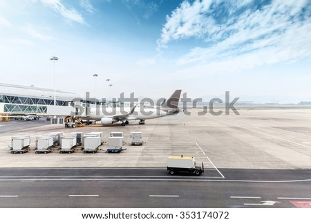 airplane on airport ramp in cloudy sky - stock photo