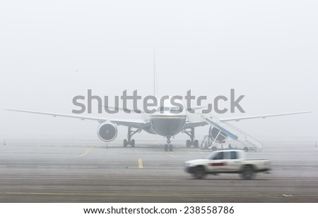 Airplane on the landing strip covered in mist and a car passing in front of it. - stock photo