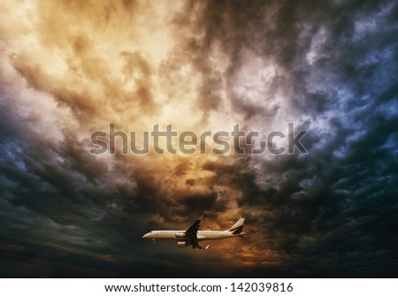 Airplane over dramatic sky backgound - stock photo