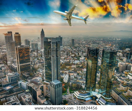 Airplane overflying modern city.