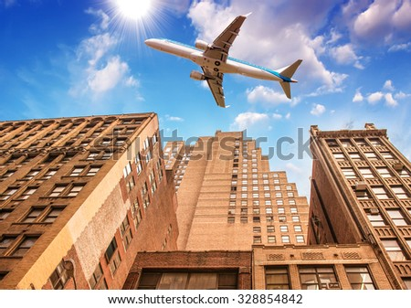 Airplane overflying modern city. - stock photo