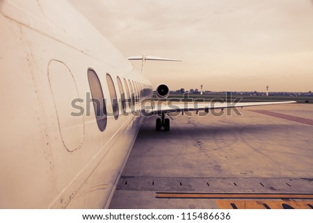 airplane parked in airport waiting for boarding passengers - stock photo