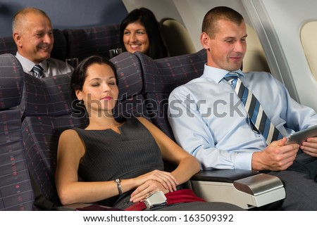 Airplane passengers relax during flight cabin sleep businesspeople - stock photo