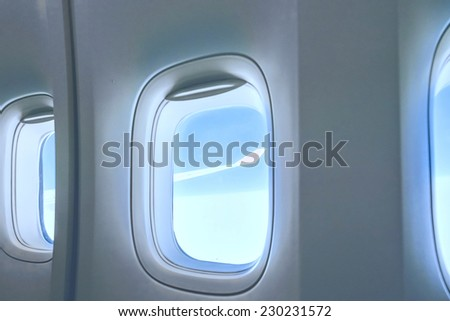 airplane porthole view into open space sky - stock photo