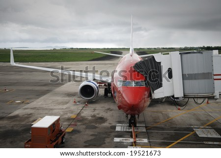 Airplane ready for boarding with stormy skies in background. - stock photo