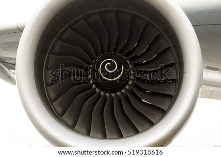 Airplane's engine closeup on a runway at an airport.