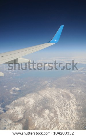 Airplane's wing under snow-covered mountains' peaks and lake - stock photo