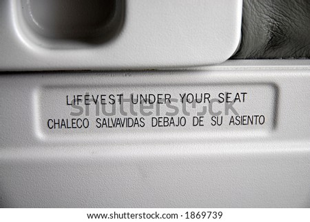 "airplane safety advice ""Life-vest under seat"" - stock photo"