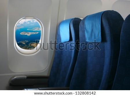 Airplane seat and window inside an aircraft with view on coast of croatia - stock photo