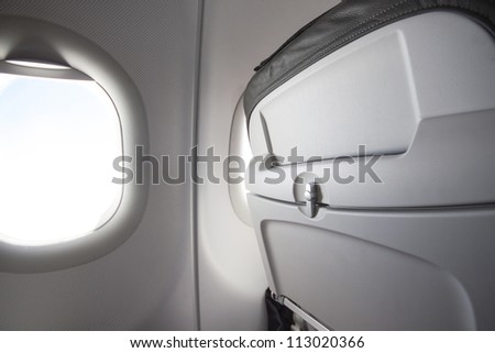 Airplane seat back and sun shining from window - stock photo