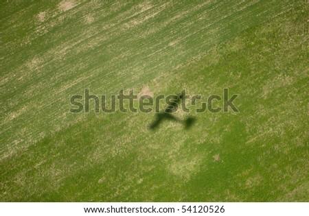Airplane shadow on big green field - stock photo