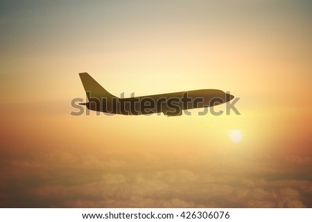 Airplane silhouette in cloudy sky at sunset - stock photo