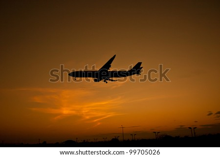 Airplane silhouette over sunset - stock photo