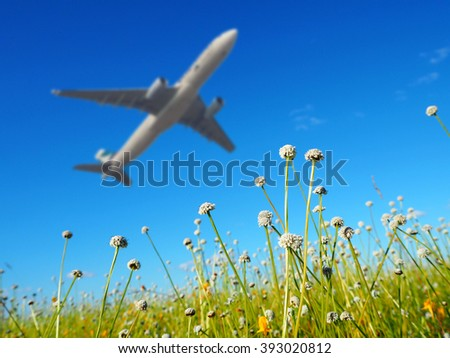Airplane takeoff on summer meadow with blue sky - stock photo