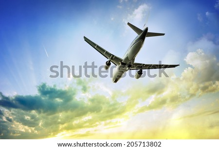 Airplane takes off in the cloudy sunset sky - stock photo