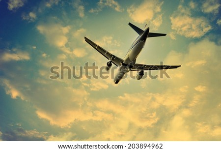 Airplane taking off and dramatic sunset sky with clouds