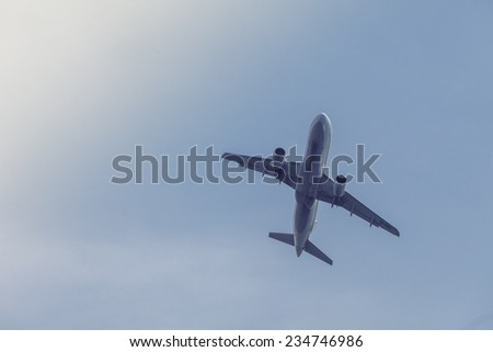 Airplane transportation. Jet air plane flies in blue sky - stock photo