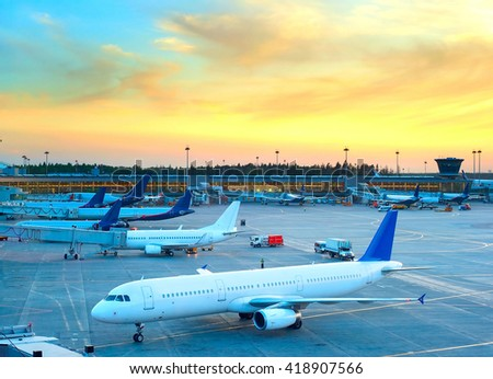 Airplane under loading in an airport at beautiful sunset - stock photo