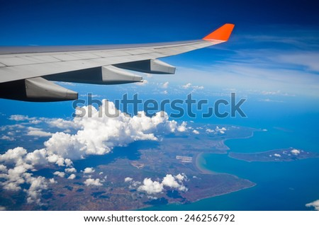 Airplane view of the wing of the plane Ocean island and clouds - stock photo