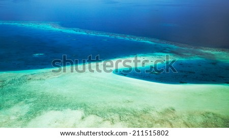 Airplane view on crystal water of Maldives sea - stock photo