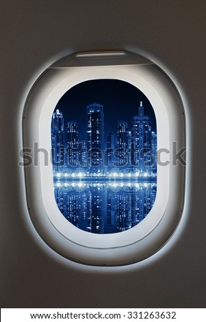 Airplane window from interior of aircraft with modern megapolis city view at night.  - stock photo