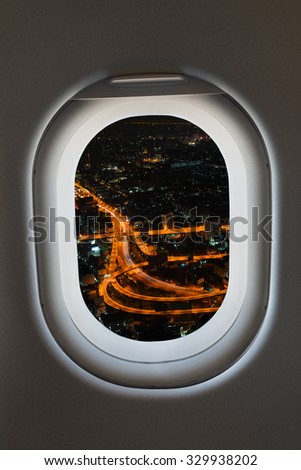 Airplane window from interior of aircraft with view of complex highway interchange at night. - stock photo