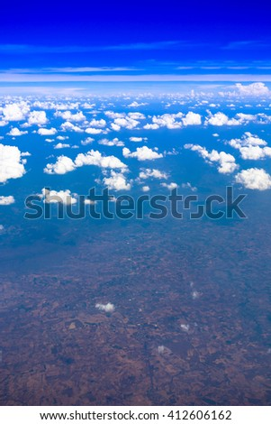 Airplane window view, cloudy clear sky - stock photo