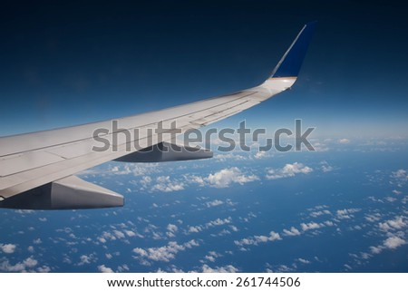 Airplane wing above ocean and Carribean Island - stock photo